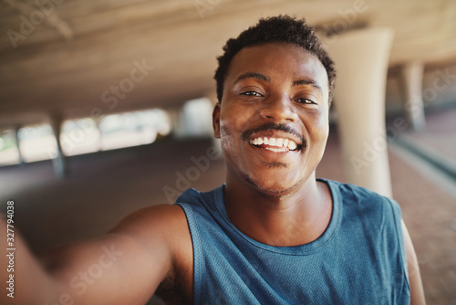 Fotografiet Portrait of a smiling young african american man taking selfie after jogging at