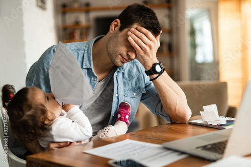 Stay at home father having a headache while babysitting and working at home Canvas Print