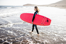 Young Woman In Wetsuit Walking...