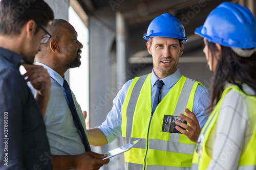 Obraz Engineers and architects in conversation at building site - fototapety do salonu
