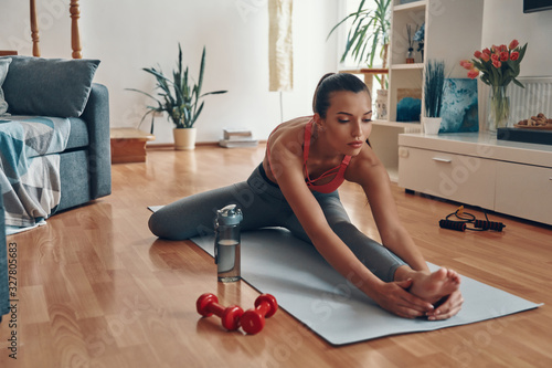 Canvastavla Attractive young woman in sports clothing stretching on exercise mat while spend