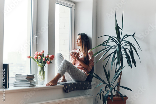 Photo Thoughtful young woman in cozy pajamas looking through the window while resting