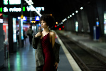 Young Stylish African-American Model Woman In Red Dress And A Fur Coat Posing On The Subway Platform At Night. Fashion And Lifestyle Concept. Nightlife In The City