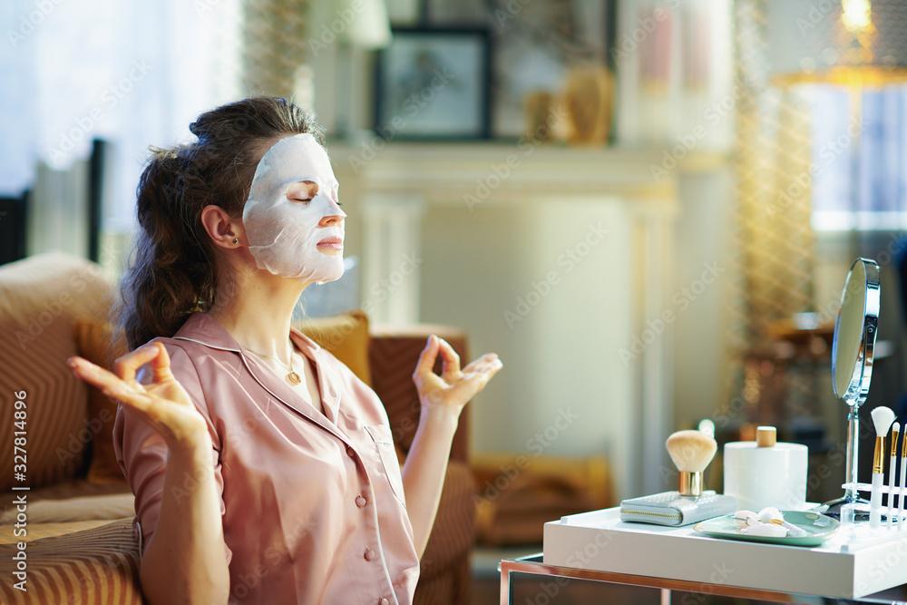 Fototapeta relaxed elegant woman with facial mask meditating