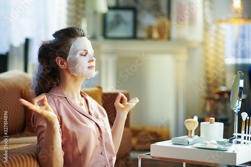 Obraz relaxed elegant woman with facial mask meditating - fototapety do salonu