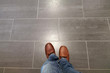 Leinwanddruck Bild - Legs in jeans and red shoes against the background of the tiled floor