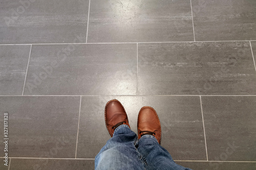 Fotografie, Obraz Legs in jeans and red shoes against the background of the tiled floor
