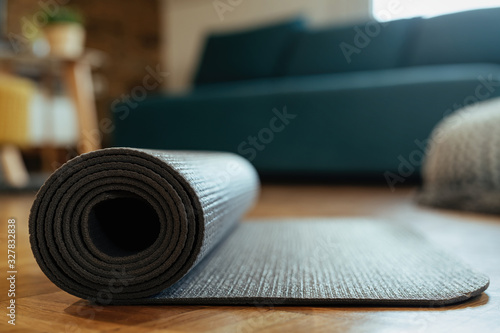 Obraz Close-up of rolled exercise mat on parquet floor. - fototapety do salonu