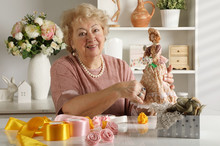 Woman Of Retirement Age Is Working On Creating A Doll In Her Workshop
