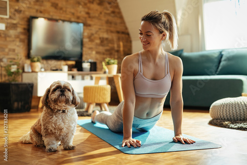 Fotomural Happy athletic woman with a dog practicing Yoga at home.