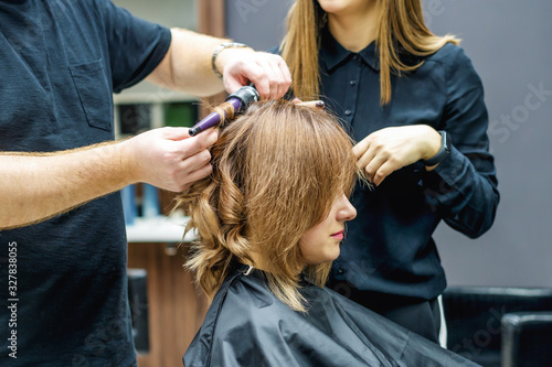 Hairdresser twisting hair of woman.