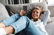 Image of smiling nice woman using cellphone while lying on sofa