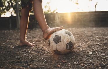 Jadno dijete koje igra stari nogomet ili nogomet na terenu s užarenom pozadinom sunčeve svjetlosti i konceptom nade.