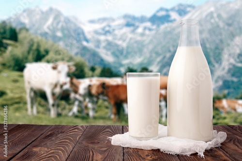 Fotografia Milk bottle and glass of milk at wooden table top on background of mountain pasture and cows herd