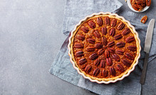 Pecan Pie, Tart In Baking Dish. Traditional Festive Thanksgiving Dessert. Grey Background. Top View.
