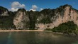 Forward drone aerial of sandy beach below steep cliffs Krabi Thailand
