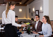 waitress bringing delicious salads to smiling people at restaurant