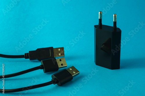 Black adapter and three usb cables on blue background. Fototapet
