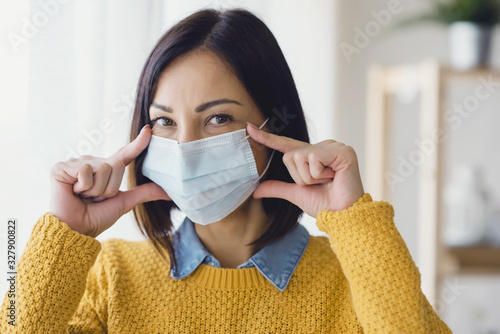 Obraz Portrait of young Asian woman,  wearing a medical surgical disposable face mask to prevent infection, virus, air pollution - fototapety do salonu