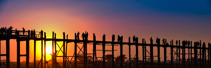 Sunset behind U Bein Bridge over Taungthaman Lake Amarapura Myanmar