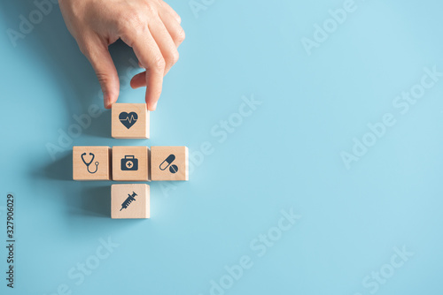 Fotografiet Health Insurance Concept, Hand of woman arranging wood cube stacking with icon healthcare medical on blue background, copy space