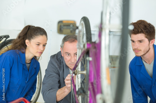Photo bike assembler with his apprentice