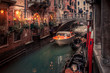 water taxi passes under a bridge on a narrow venice canal
