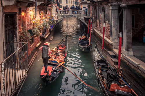 Photo Gondolier rowing down a narrow canal in venice with christmas lights illuminatin
