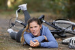 young woman fallen from bicycle and holding her elbow