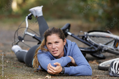 Obraz young woman fallen from bicycle and holding her elbow - fototapety do salonu