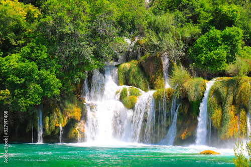 A picturesque cascade waterfall among large stones in the Krka National Landscape Park, Croatia in spring or summer. The beautiful Croatian waterfalls, mountains and nature. © rospoint
