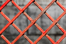 Red, Textured Metal Fence, Close-up, Pattern. Wallpaper With Interesting, Vintage Architectural Details. Steel Lattice Hedge Which Painted With Bright Red Paint. Background With Wattle Iron Elements.