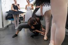 Female Director Tying Ballet Shoes On Ballerina Backstage