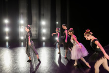 Female Dance Instructor Leading Ballerinas On Stage