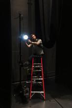 Male Stage Manager On Ladder Adjusting Spotlight