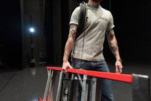 Male Stage Manager Carrying Ladder