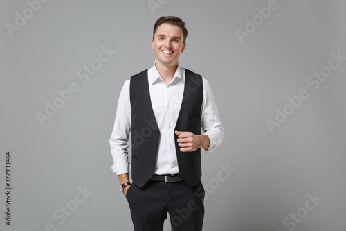Slika na platnu Smiling cheerful young business man in classic black waistcoat shirt posing isolated on grey wall background in studio