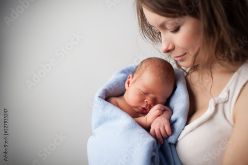 Close up of beautiful young woman holding adorable baby wrapped in blue blanket Wallpaper Mural