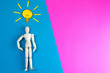 Leinwandbild Motiv Wooden figurine of a man with a light bulb with yellow craft paper over his head on a blue and pink background with clear space for text