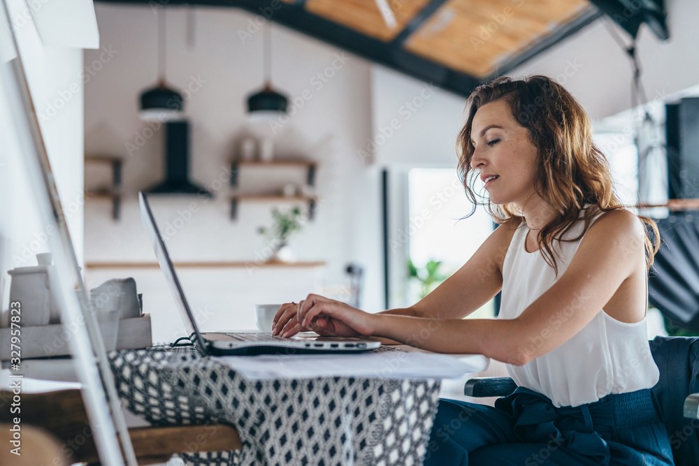 Fototapeta Woman using laptop while sitting at home. Young woman sitting in kitchen and working on laptop.