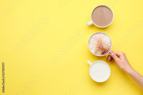 Female hand with cups of coffee on color background Wallpaper Mural