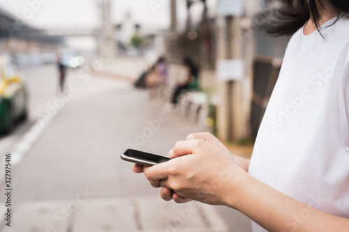 Asian young woman waiting for the bus at bus stop in the crowded and busy city and touching on smartphone for searching a map Fototapet