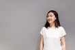 Beautiful young Asian ethnicity woman portrait on the grey concept wall with copy space close up.