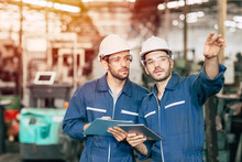Two Engineer Worker Working Together With Safety Uniform And White Helmet To Work In Industry Factory Handle Tablet.