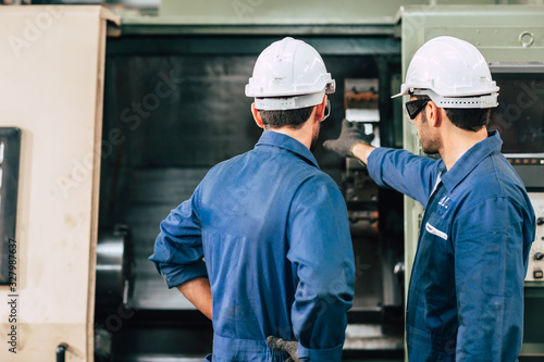 Fototapeta machine maintenance service engineer team working together teamwork in factory back view. obraz
