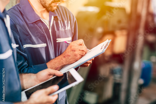 Fotografía worker taking note using pen and paper with new young engineer using computer tablet for work faster and more efficiency