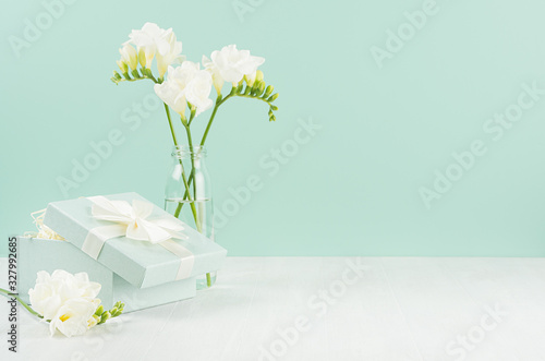 Romantic bright holiday background with spring flowers freesia in glass vase and ajar gift box with ribbon in green mint menthe interior on white board Canvas Print