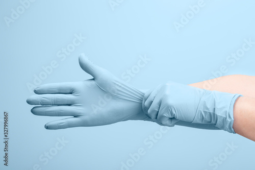 Photo Female doctor's hands putting on blue sterilized surgical gloves