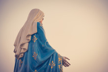 The Blessed Virgin Mary Statue Figure In A Sunset Time. Catholic Praying For Our Lady - The Virgin Mary.