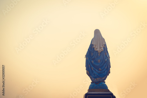 Fotografía Silhouettes of the blessed Virgin Mary statue figure in a warm tone - sunset scene